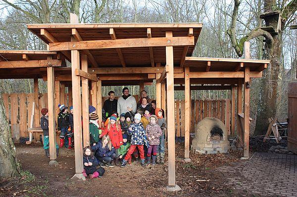 Kinder und Betreuer der Naturwerkstatt stehen unter der geförderten Überdachung